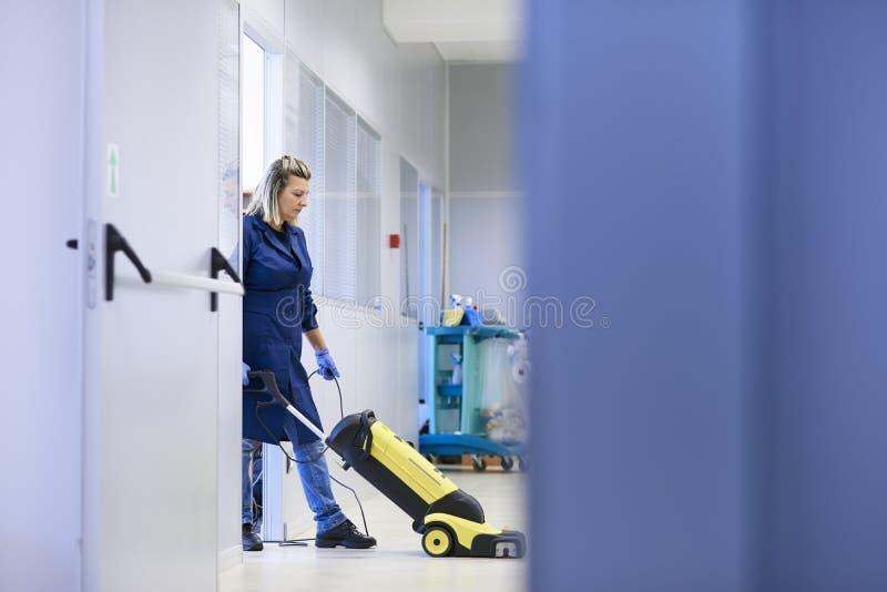 Mujeres en el lugar de trabajo, suelo que se lava del producto de limpieza de discos femenino profesional adentro foto de archivo libre de regalías