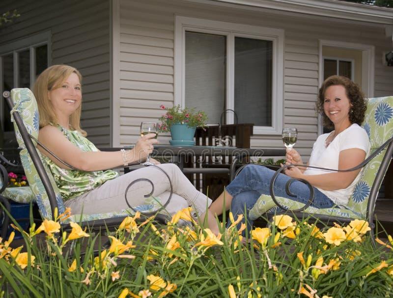 Mujeres en el patio enmarcado por las flores foto de archivo