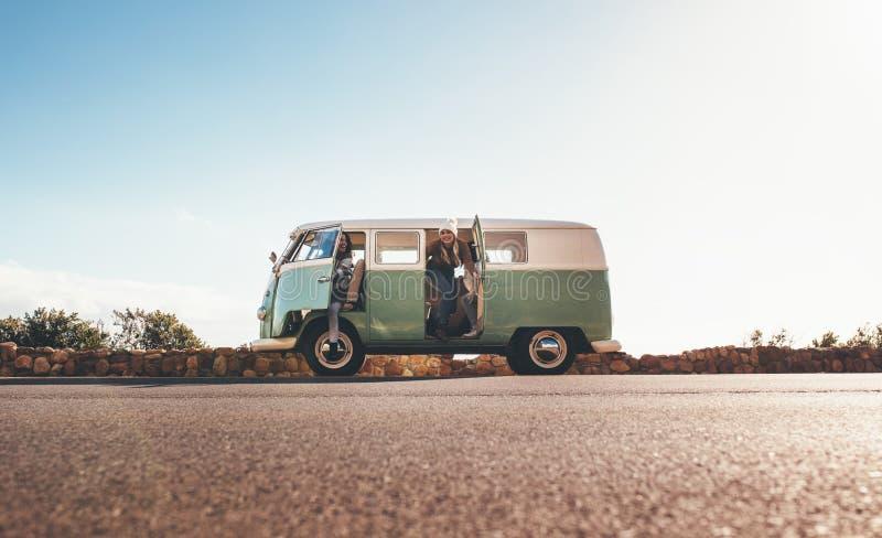 Mujeres en el roadtrip que viaja junto en una furgoneta imagen de archivo
