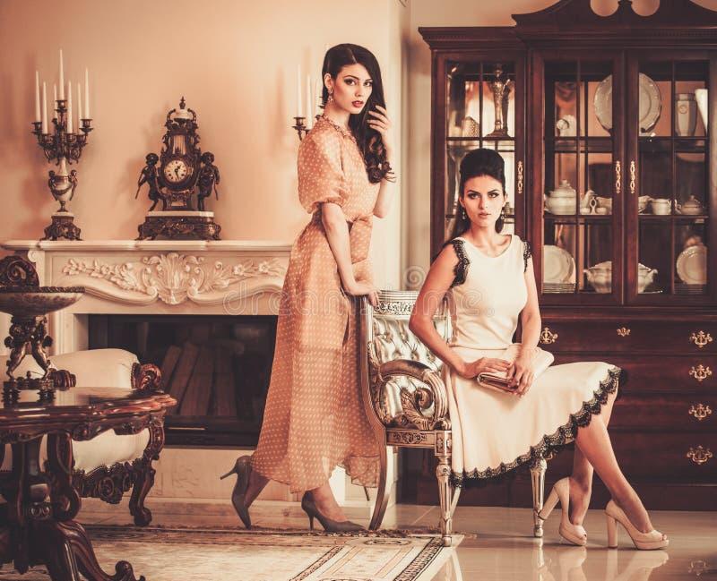 Mujeres en interior de lujo de la casa foto de archivo libre de regalías