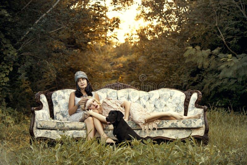 Mujeres en la moda de los años 20 en el sofá del vintage imagen de archivo libre de regalías