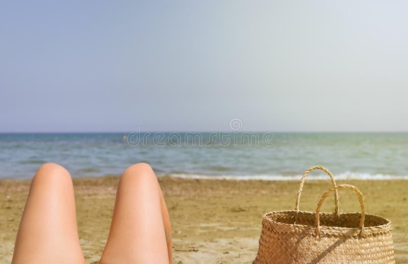 Mujeres en las vacaciones que relajan y que consiguen a Tan On Sunny Day Beach imagen de archivo