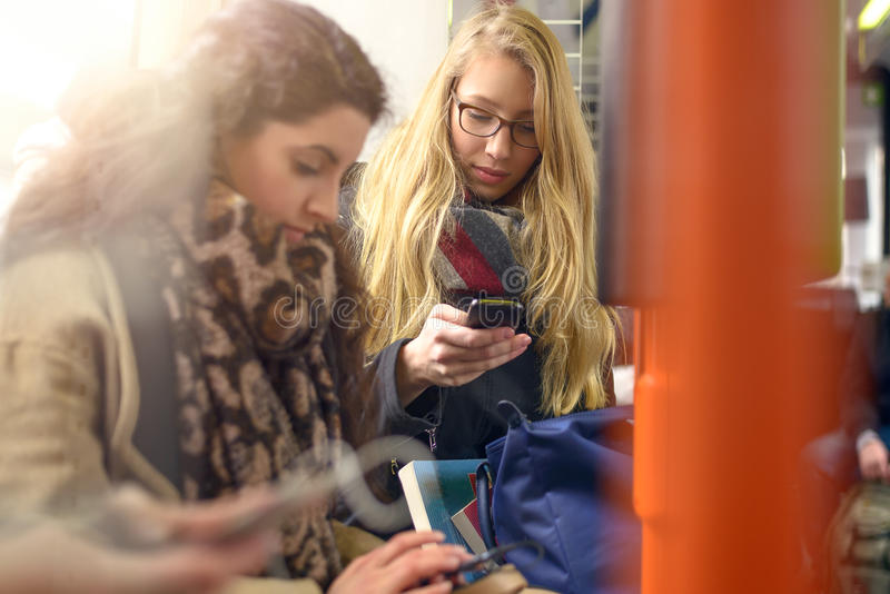 Mujeres en los abrigos de invierno que se sientan en el tren de cercanías fotos de archivo