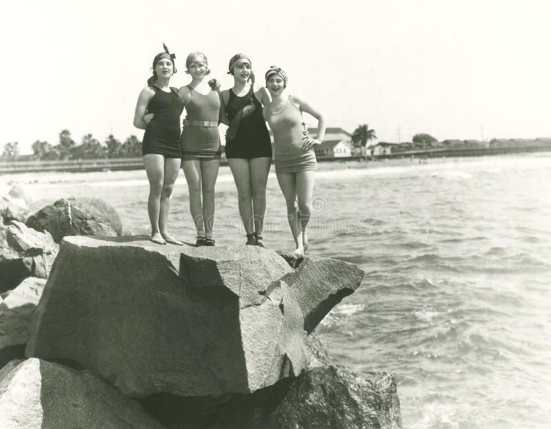 Mujeres en los bañadores que presentan en roca imagen de archivo