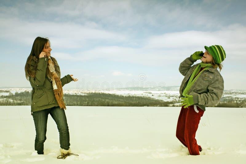 Mujeres en los teléfonos celulares en invierno foto de archivo libre de regalías