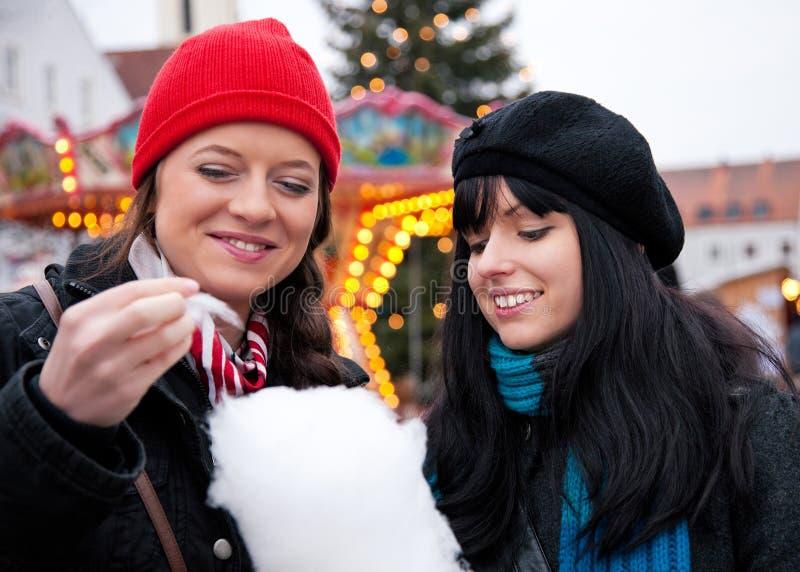 Mujeres en mercado de la Navidad que comen el caramelo foto de archivo