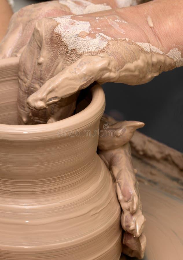 Mujeres en vías de la fabricación del florero de la arcilla en la rueda de la cerámica foto de archivo