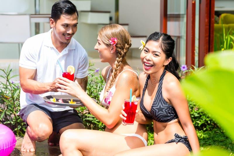 Mujeres en vacaciones en la piscina asiática del hotel con los cócteles imágenes de archivo libres de regalías