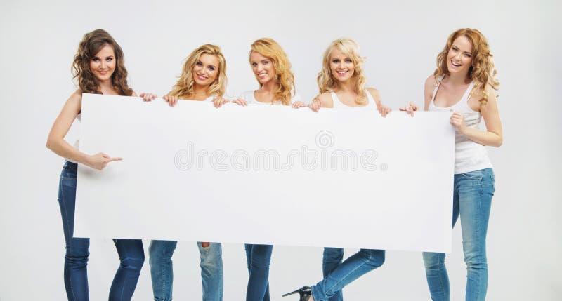 Mujeres encantadoras y tranquilas que llevan a cabo a un tablero imagenes de archivo
