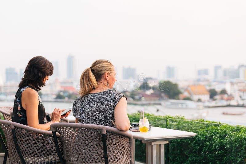 Mujeres europeas que sientan y que miran una opinión Wat Arun The Temple del amanecer cerca del río de Chaophraya por la tarde en foto de archivo libre de regalías