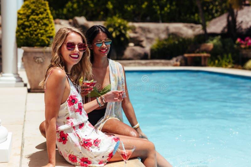 Mujeres felices con las bebidas que se relajan en el poolside imagen de archivo libre de regalías