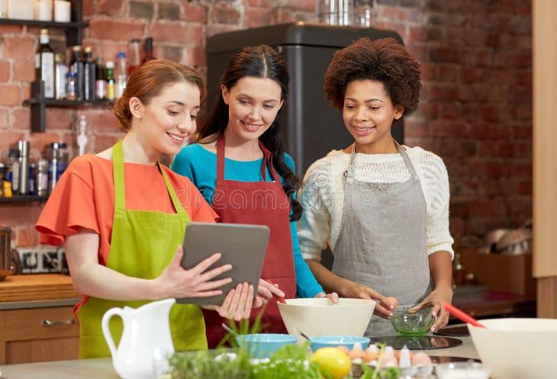 Mujeres felices con PC de la tableta que cocinan en cocina fotos de archivo libres de regalías