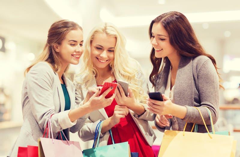 Mujeres felices con smartphones y panieres foto de archivo libre de regalías