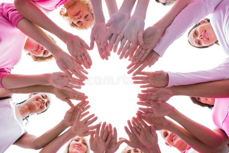 Mujeres felices en el rosa que lleva del círculo para el cáncer de pecho foto de archivo libre de regalías