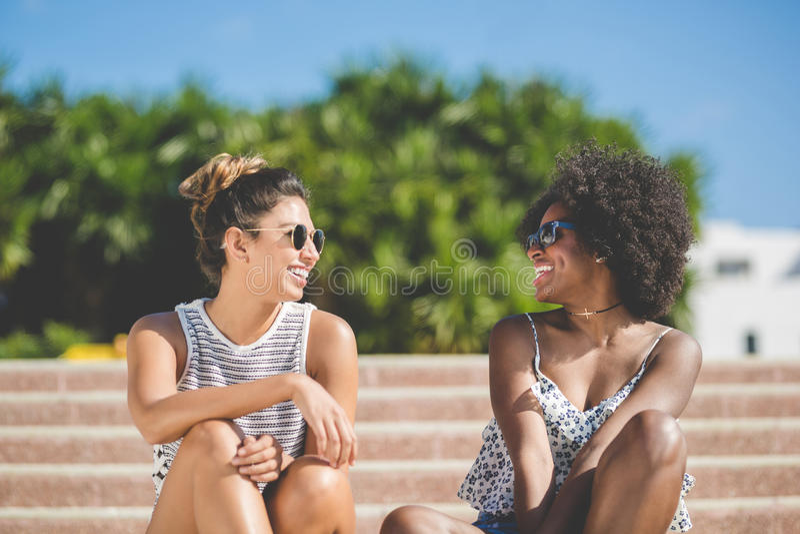 Mujeres felices jovenes que se sientan en hablar de las escaleras foto de archivo