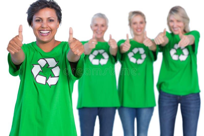 Mujeres felices que llevan las camisetas de reciclaje verdes que dan los pulgares para arriba fotos de archivo