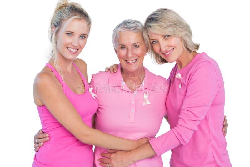 Mujeres felices que llevan los tops y las cintas rosados para el cáncer de pecho imagenes de archivo