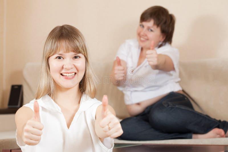 Mujeres felices que muestran el pulgar encima de la muestra fotos de archivo libres de regalías