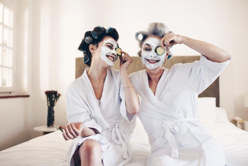 Mujeres felices que se sientan en cama en las albornoces que ponen en la cara m de la belleza imagen de archivo