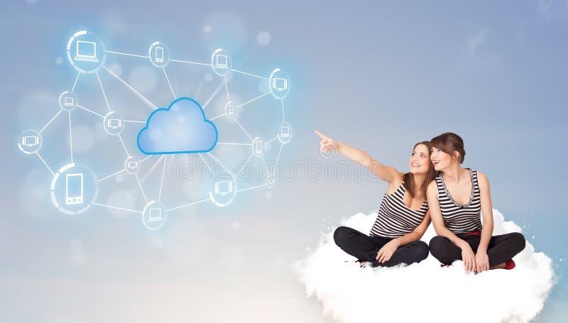 Mujeres felices que se sientan en clous con la computación de la nube imagen de archivo libre de regalías