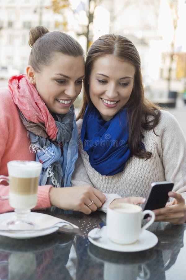 Mujeres felices que usan el teléfono celular en el café de la acera imagen de archivo libre de regalías