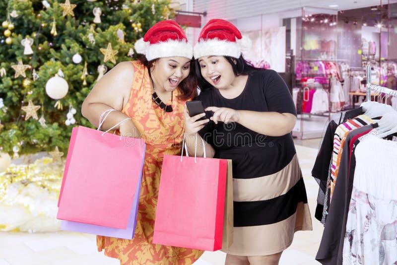 Mujeres gordas con el sombrero y el smartphone de Papá Noel imágenes de archivo libres de regalías