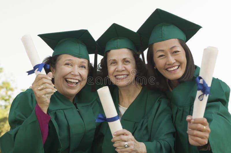 Mujeres graduadas multiétnicas imagen de archivo