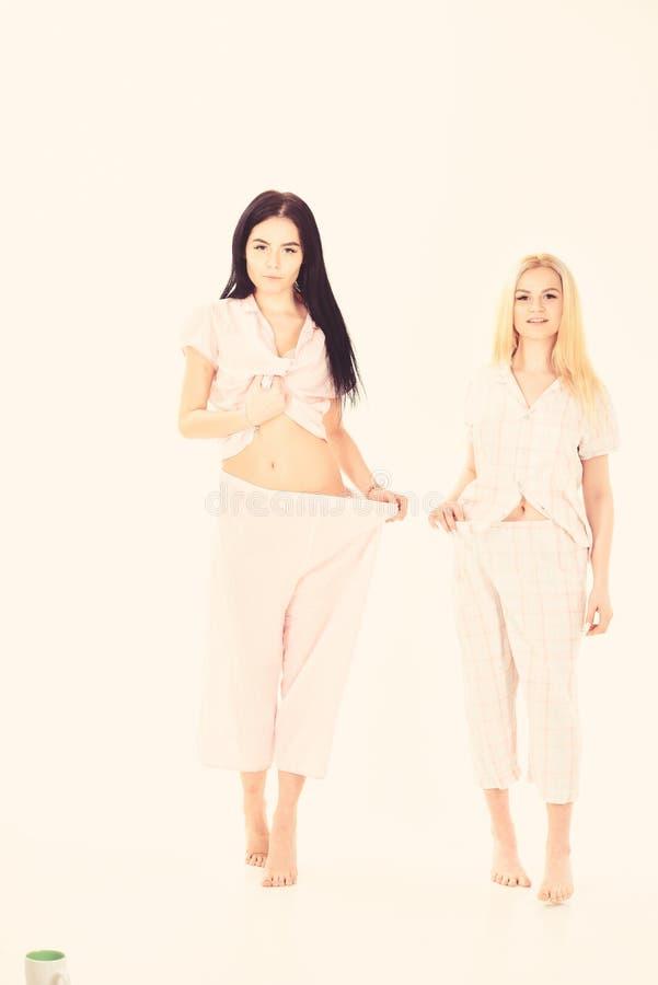 Mujeres, hermanas jovenes atractivas, amigos en pijamas Concepto del resultado de la p?rdida de peso Las muchachas en cara pensat imagenes de archivo