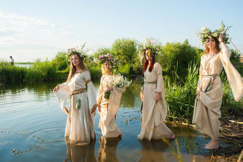 Mujeres hermosas con la guirnalda de la flor en agua fotografía de archivo libre de regalías