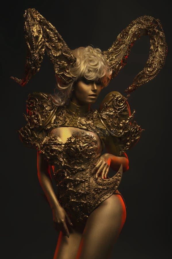 Mujeres hermosas del diablo con los cuernos ornamentales de oro fotos de archivo libres de regalías