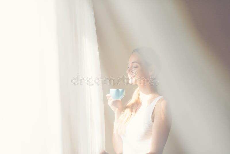 Mujeres hermosas jovenes que beben el café en el dormitorio del mornng cerca de ventana con la capa blanca de la cortina Muchacha imagen de archivo