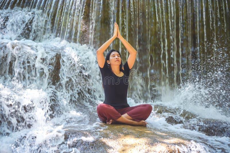 Mujeres hermosas jovenes que hacen actitud que se sienta de la yoga en la cascada foto de archivo