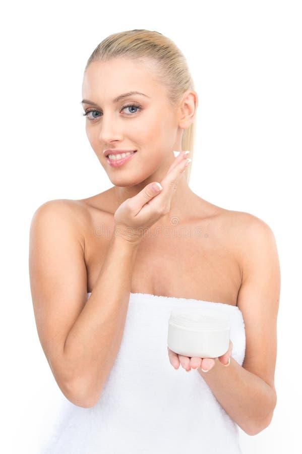 Mujeres hermosas que aplican la crema cosmética de la crema hidratante en cara fotografía de archivo libre de regalías