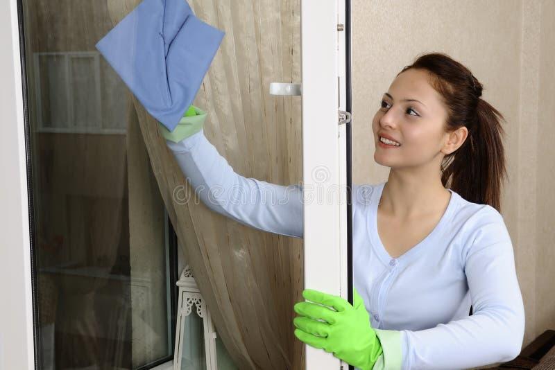 Mujeres hermosas que limpian una ventana imagen de archivo