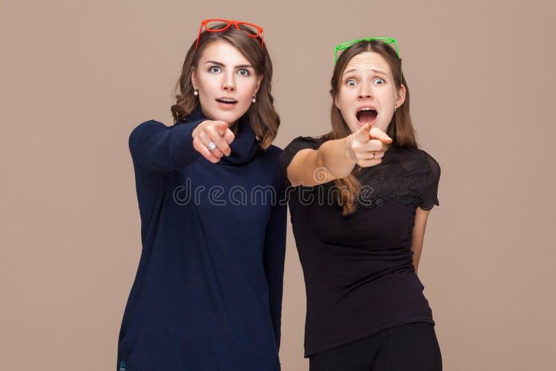 Mujeres hermosas que se colocan cerca de uno a y que señalan los fingeres en fotografía de archivo