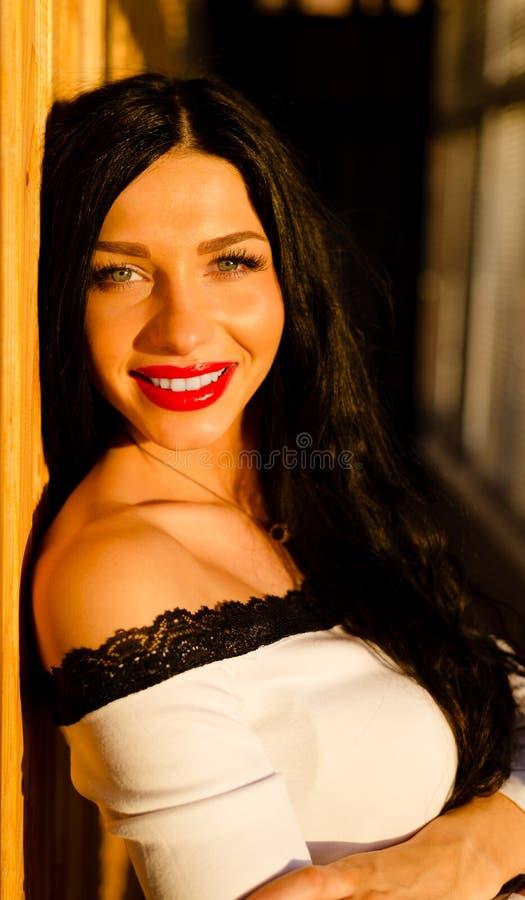 Mujeres hermosas que sonríen cerca de ventana en puesta del sol imagenes de archivo