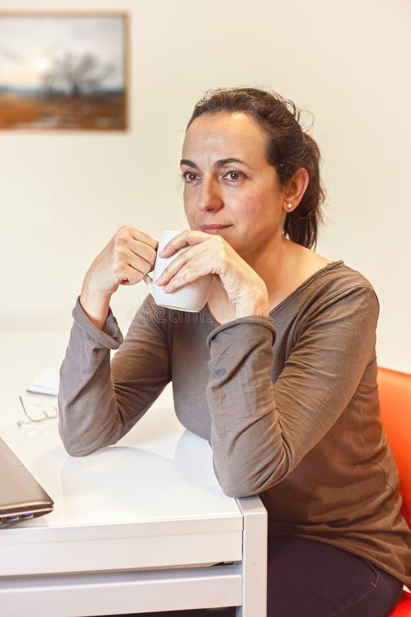 Mujeres hispánicas jovenes bonitas que se sientan en la tabla en casa y que beben cualquier cosa imágenes de archivo libres de regalías