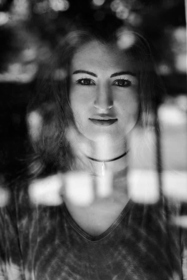 Mujeres hispánicas que miran en la cámara a través de una ventana imagen de archivo