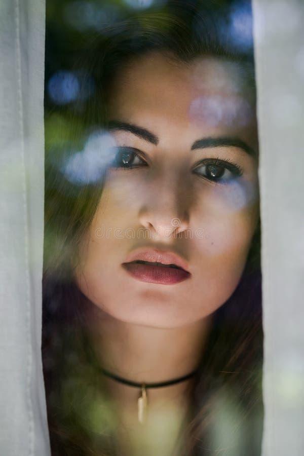 Mujeres hispánicas que miran en la cámara a través de una ventana imagen de archivo libre de regalías