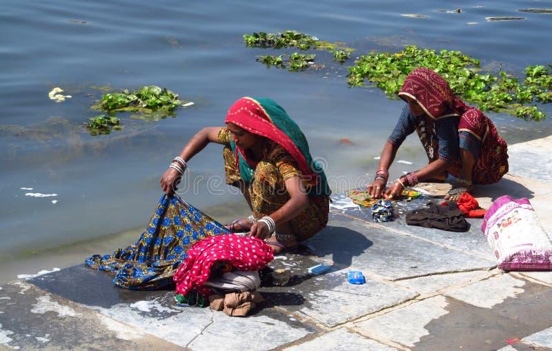 Mujeres indias jovenes pobres que lavan su ropa en un lago fotos de archivo