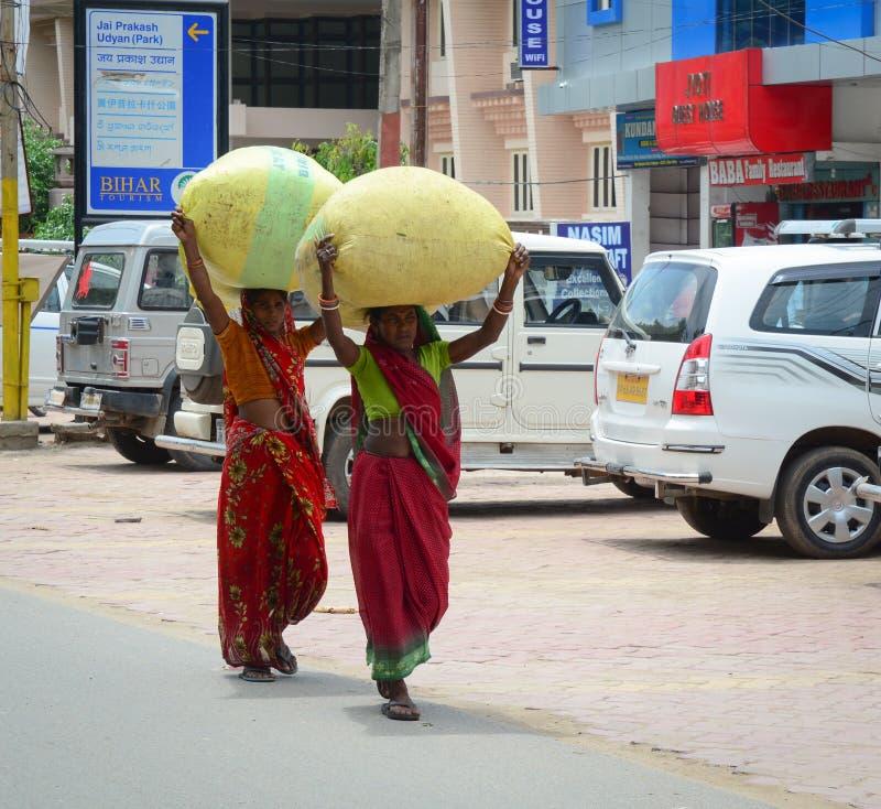 Mujeres indias que llevan mercancías en la calle en Bodhgaya, la India fotografía de archivo