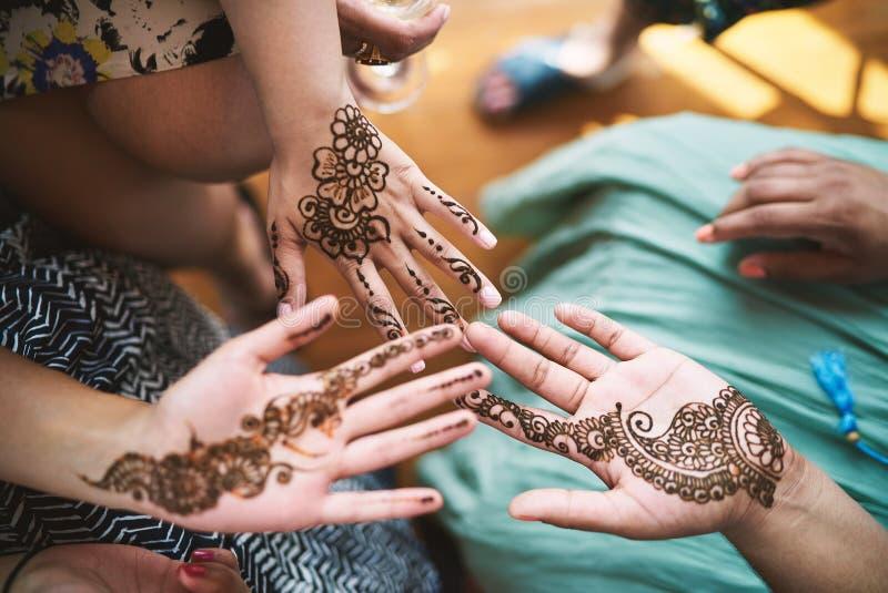 Mujeres indias que muestran la mano con el arte Mehndi del tatuaje de la alheña fotografía de archivo