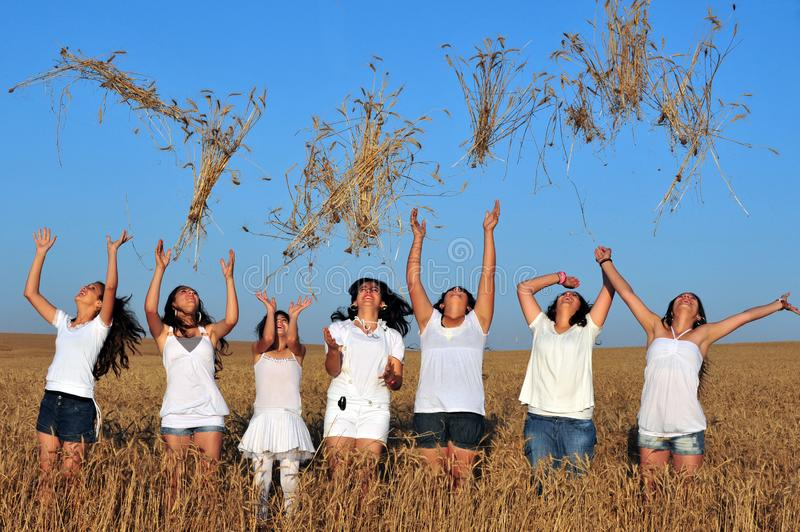 Mujeres israelíes jovenes felices que lanzan trigo al aire en Shavuot J foto de archivo libre de regalías