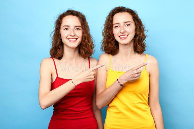 Mujeres jovenes alegres alegres vestidas en la camiseta roja y amarilla que señala el finger lejos imagenes de archivo