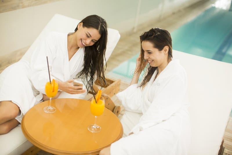Mujeres jovenes atractivas en las albornoces que se relajan en jui de consumición del balneario fotos de archivo