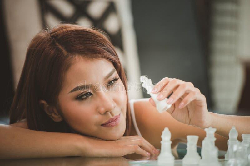 Mujeres jovenes atractivas que juegan al juego de mesa del ajedrez imagen de archivo