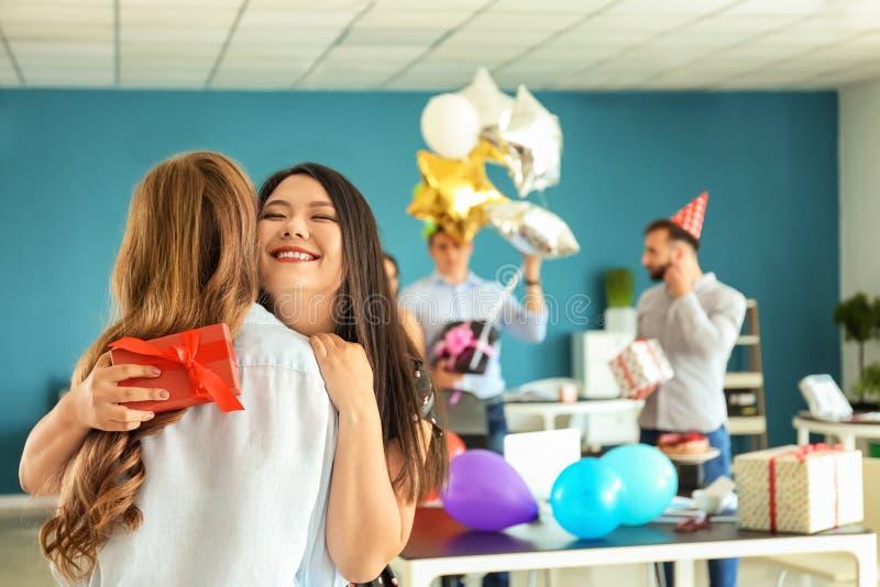 Mujeres jovenes con la caja de regalo que abraza en la fiesta de cumpleaños en oficina imágenes de archivo libres de regalías