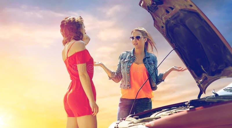 Mujeres jovenes con la capilla abierta del coche quebrado fotografía de archivo libre de regalías