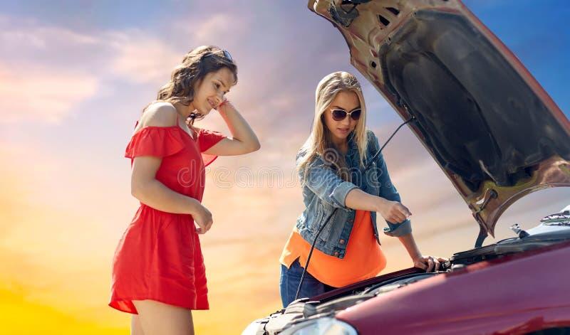 Mujeres jovenes con la capilla abierta del coche quebrado foto de archivo libre de regalías
