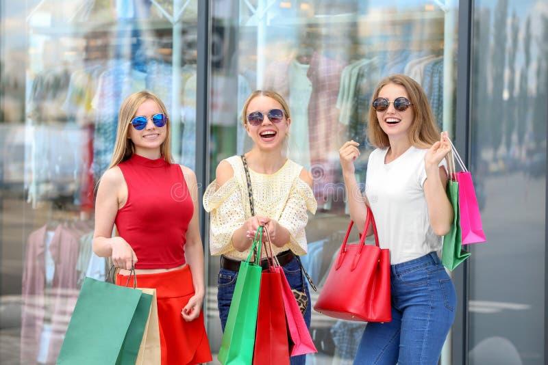 Mujeres jovenes con los bolsos de compras en la calle de la ciudad imágenes de archivo libres de regalías